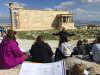 Professor lecturing group of students in front of Greek ruins.
